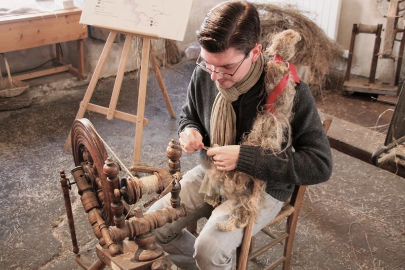 Julien, animateur de la Fabrique, ancienne «Maison des tisserands» travaille sur un rouet, une invention de Léonard de Vinci. On y entraînait les enfants dès 7 ans, pourqu'ils soient compétents à 14.